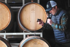 A wine maker tasting his wine from the barrel